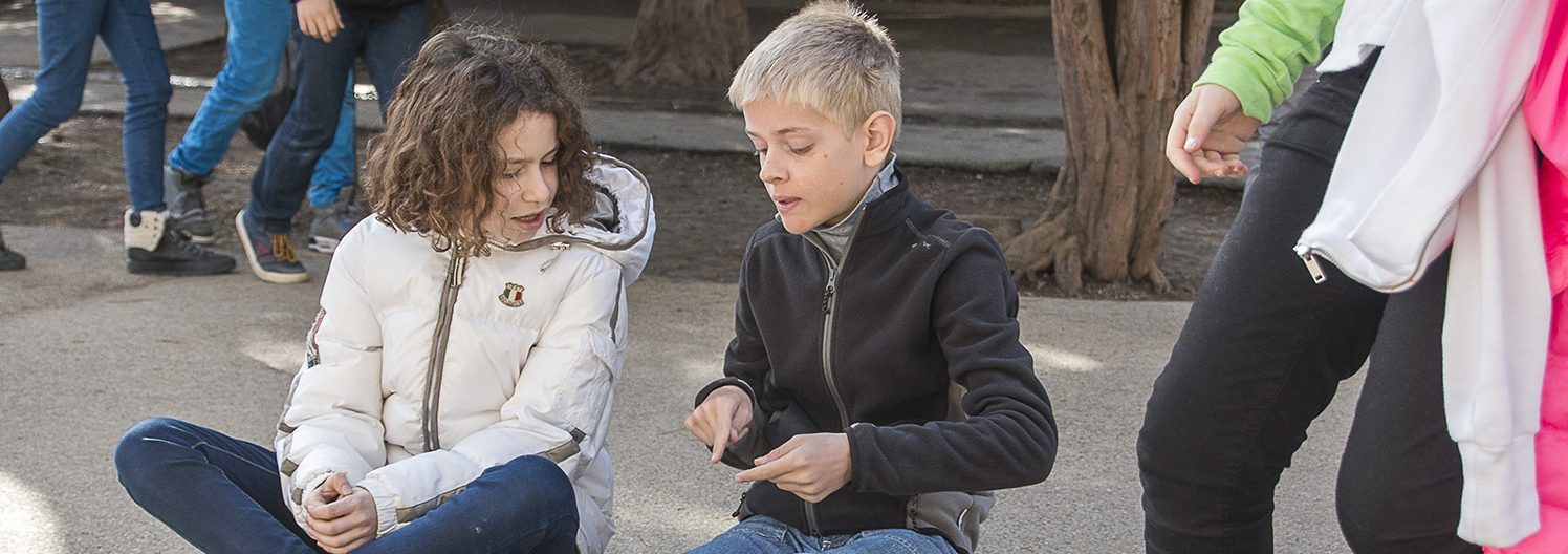 Une enfant anglais et une enfant française en pleine conversation dans la cour de l'école Greenfield