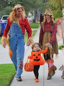 photo de parents déguisés en épouvantail accompagnant une petite fille déguisée en citrouille